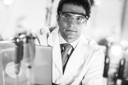 Portrait of a confident male engineer in his working environment. Science and technology concept. Black and white image.