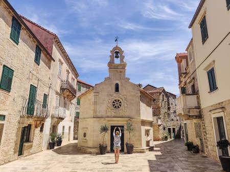 Female tourist taking photo of mall church on square of small urban village of Stari grad on Hvar island in Croatia, Adriatic Sea, Europe. Banco de Imagens