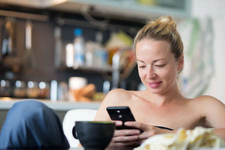 Young smiling cheerful woman indoors at home kitchen using social media on phone for video chatting and staying connected with her loved ones. Stay at home, social distancing lifestyle.