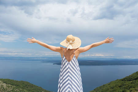 Rear view of young woman wearing striped summer dress and straw hat standing in super bloom of wildflowers, relaxing with hands up to the sky, enjoing beautiful view of Adriatic sea nature, Croatia.