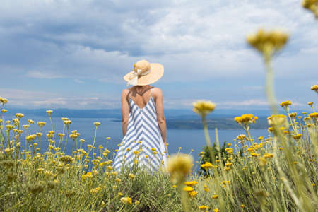 Rear view of young woman wearing striped summer dress and straw hat standing in super bloom of wildflowers, relaxing while enjoing beautiful view of Adriatic sea nature, Croatia. Focus on flowers. Banco de Imagens