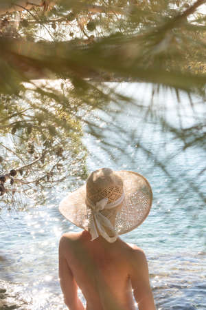 Rear view of topless beautiful woman wearing nothing but straw sun hat realaxing on wild coast of Adriatic sea on a beach in shade of pine tree. Relaxed healthy lifestyle concept.