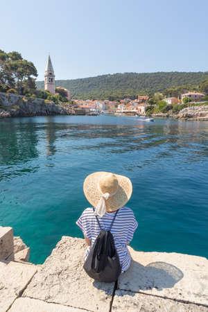 Woman traveler wearing straw summer hat and backpack, sittingat edge of stone pier, enjoying beautiful panoramic view of Veli Losinj, Losinj island, Croatia.