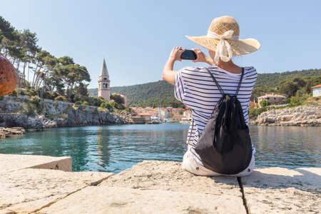 Woman traveler wearing straw summer hat and backpack, sittingat edge of stone pier, taking photo of beautiful panoramic view of Veli Losinj, Losinj island, Croatia.