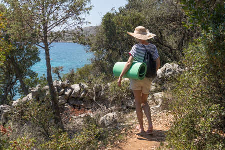Young active feamle tourist wearing small backpack and yoga mat walking on coastal path among pine trees looking for remote cove to swim alone on seaside in Croatia. Travel and adventure concept.