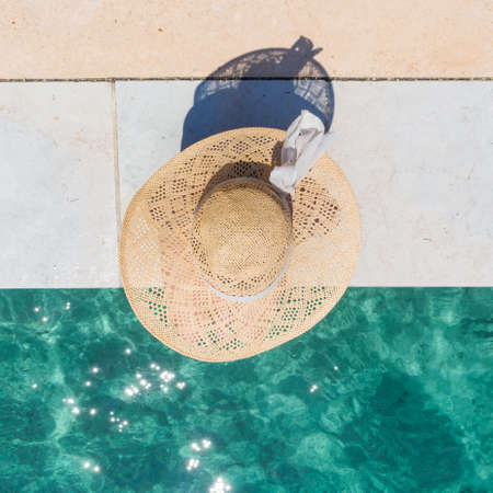 Graphic image of top down view of woman wearing big summer sun hat relaxing on pier by clear turquoise sea.