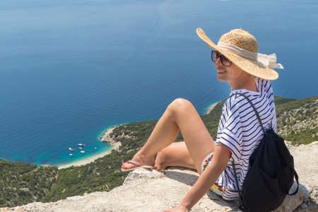Active sporty woman on summer vacations sitting on old stone wall at Lubenice village, wearing straw hat and beach backpack enjoying beautiful coastal view of Cres island, Croatia.