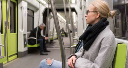 Portrait of lovely girl commuting on almost empty public subway train. Staying at home and social distancing recomented due to corona virus pandemic outbreak.