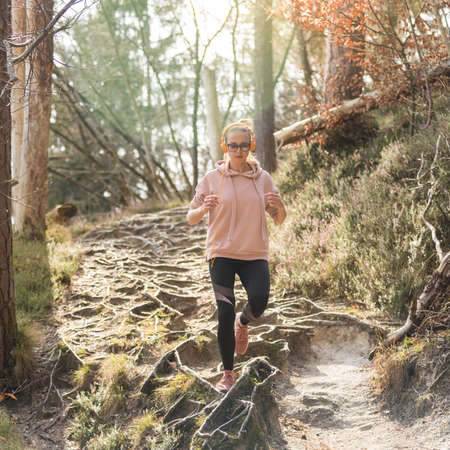 Active sporty woman listening to the music while running in autumn fall forest. Female runner training outdoor. Healthy lifestyle image of young caucasian woman jogging outside.