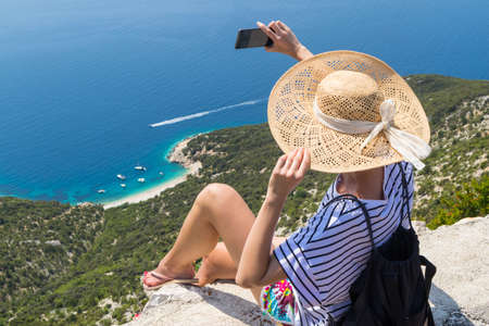 Active sporty woman on summer vacations taking selfie picture while enjoying beautiful coastal view of Cres island, Croatia from Lubenice traditional costal village.