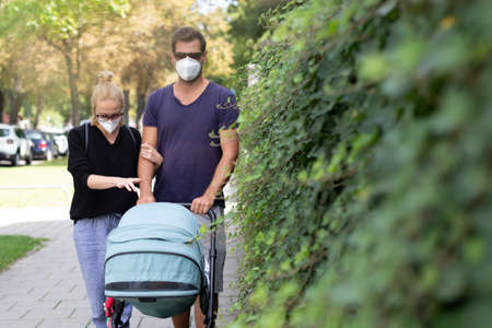 Worried young parent walking on empty street with stroller wearing medical masks to protect them from corona virus. Social distancing life during corona virus pandemic. Banco de Imagens