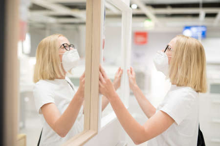 New normal during covid epidemic. Caucasian woman shopping at retail furniture and home accessories store wearing protective medical face mask to prevent spreading of corona virus.