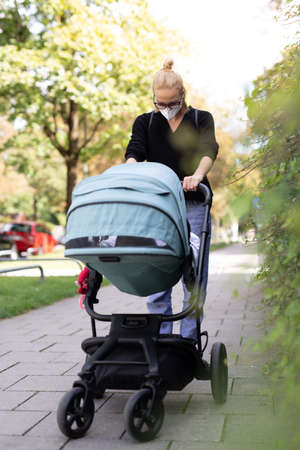 Worried young mom walking on empty street with stroller wearing medical masks to protect her from corona virus. Social distancing life during corona virus pandemic.