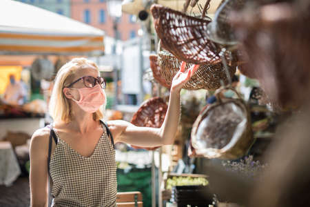 Casual woman shopping outdoor at open market stalls wearing fase masks for protection from corona virus pandemic in Munchen, Germany. New normal. Banco de Imagens