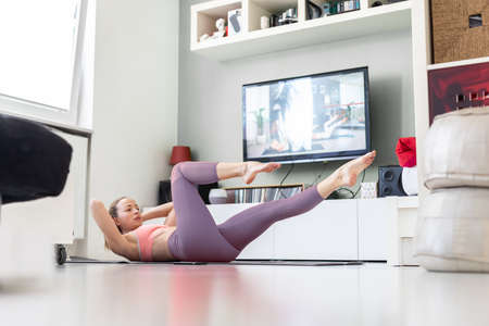 Attractive sporty woman working out at home, doing pilates exercise in front of television in small studio appartment. Social distancing. Stay healthy and stay at home during corona virus pandemic.