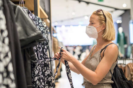 Fashionable woman wearing protective face mask shopping clothes in reopen retail shopping store. New normal lifestyle during corona virus pandemic. Banco de Imagens