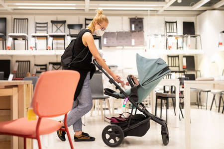 Young mom with newborn in stroller shopping at retail furniture and home accessories store wearing protective medical face mask to prevent spreading of corona virus. New normal during covid epidemic.