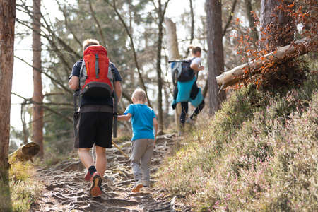 Rear view of unrecognizable young active family hiking together on mountain forest trackin in fall. Parents wearing backpacks and child toys. Active lifestyle in nature concept.
