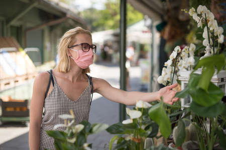 Casual woman shopping for plants outdoor at open market stalls wearing fase masks for protection from corona virus pandemic in Munchen, Germany. New normal. Stock fotó