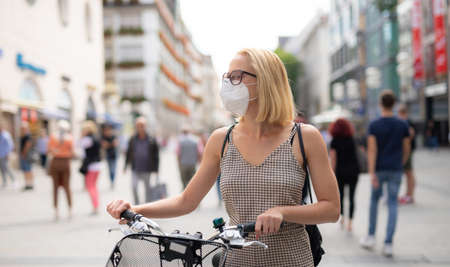 Woman walking by her bicycle on pedestrian city street wearing medical face mask in public to prevent spreading of corona virus. New normal during covid epidemic. Social responsibility. Stock Photo