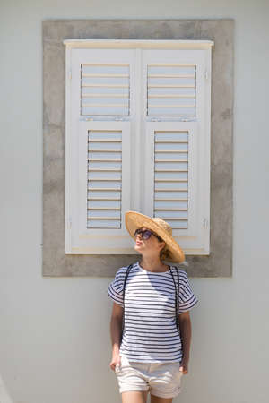Beautiful young female tourist woman wearing sun hat, standing and relaxing in front of vinatage wooden window in old Mediterranean town while sightseeing on hot summer day. 版權商用圖片