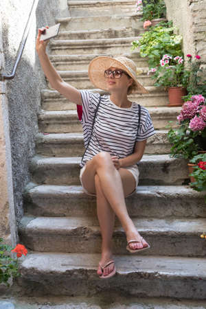 Beautiful female tourist wearing big straw sun hat and shorts sitting and relaxing on old stone house stairs during summer travel on Mediterranean cost on hot summer day and taking selfie. 版權商用圖片