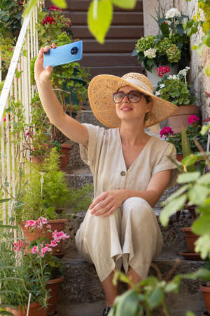 Beautiful female tourist wearing big straw sun hat and shorts sitting and relaxing on old stone house stairs during summer travel on Mediterranean cost on hot summer day and taking selfie. Imagens