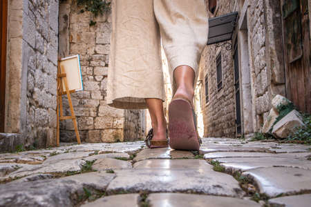 Detail shot of female legs wearing comfortable travel sandals walking on old medieval cobblestones street dring sightseeing city tour. Travel, tourism, and adventure concept. Imagens