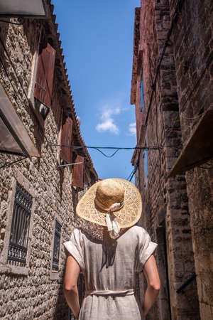 Rear view of beautiful blonde young female traveler wearing straw sun hat sightseeing and enjoying summer vacation in an old traditional costal town at Adriatic cost, Croatia.