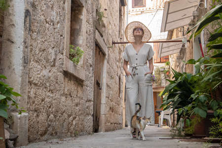 Beautiful blonde young female traveler wearing straw sun hat sightseeing and enjoying summer vacation in an old traditional costal town at Adriatic cost, Croatia. Imagens