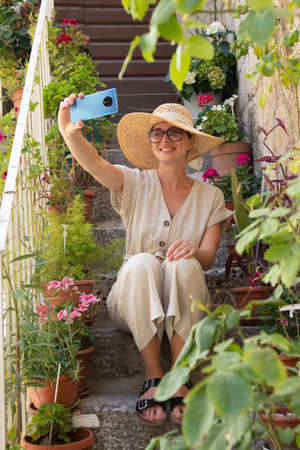 Beautiful female tourist wearing big straw sun hat and shorts sitting and relaxing on old stone house stairs during summer travel on Mediterranean cost on hot summer day and taking selfie.. Imagens