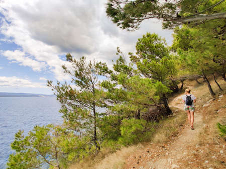 Young active feamle tourist wearing small backpack walking on coastal path among pine trees looking for remote cove to swim alone in peace on seaside in Croatia. Travel and adventure concept.