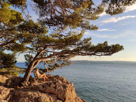 Pensive woman on vacations, sitting and relaxing under large pine tree on bench by dip blue sea enjoying beautiful sunset light in Brela, Makarska region, Dalmatia, Croatia.