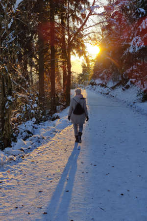 Woman hiking on snow in white winter forest berore the sunset. Recreation and healthy lifestyle outdoors in nature. Imagens