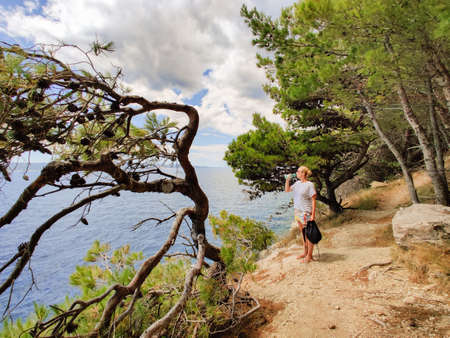 Young active feamle tourist taking a break, drinking water, wearing small backpack while walking on coastal path among pine trees looking for remote cove to swim alone in peace on seaside in Croatia. Imagens
