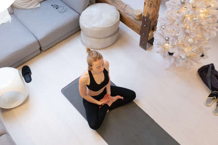 Beautiful blonde woman doing home workout indoors. Woman practice yoga at home. Fit girl using workout tutorials for healthy active lifestyle. Woman using quarantine for home workouts and stretching
