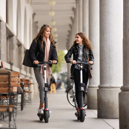 Trendy fashinable teenager girls riding public rental electric scooters in urban city environment. New eco-friendly modern public city transport in Ljubljana, Slovenia.