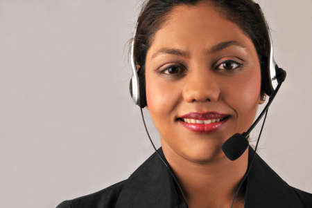 Smiling young Indian woman of a call center  photo