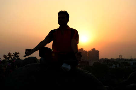 Young man meditating in the evening