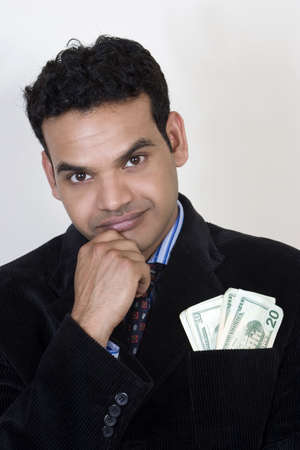 Indian man thinking with money in pocket