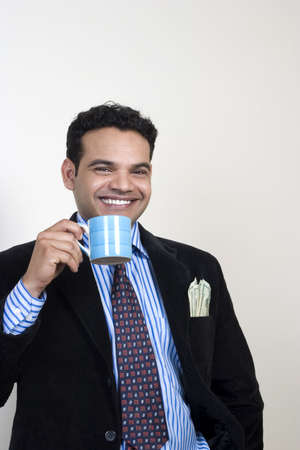 portrait of successful relaxed Indian having coffee photo