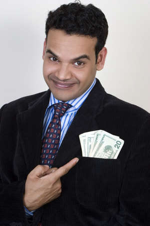 Successful Indian pointing to  money in pocket Stock Photo