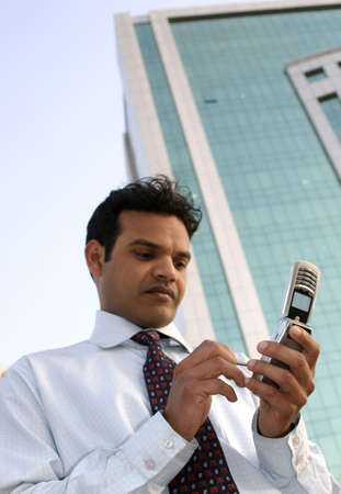 Indian Business man using a mobile phone standing outside a modern office building Stock Photo