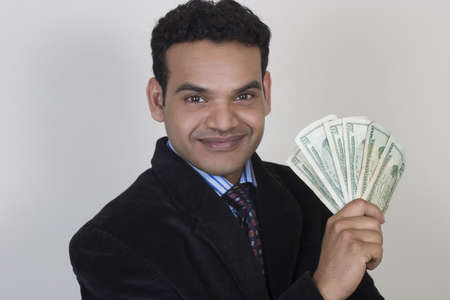 successful Indian man with money fan