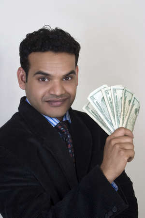 Young Indian man with dollars