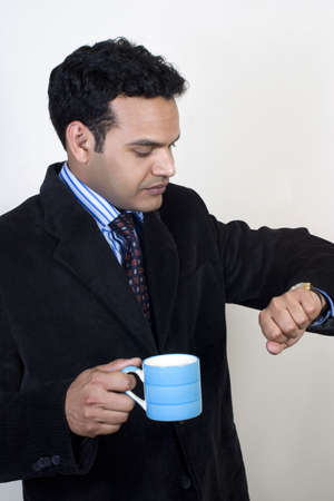 young business man having coffee break and looking at watch