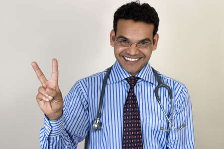 young Indian doctor giving two advices with smile