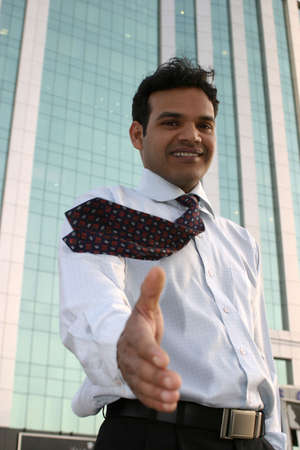 young indian business man shaking hands with office building backdrop photo