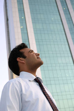 Young Man Looking Up at a highrise building with dreams in his eyes photo