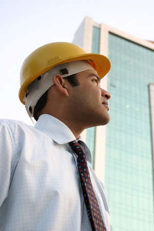 executive helmet: Young Indian Engineer with Vision looking up at a high rise building